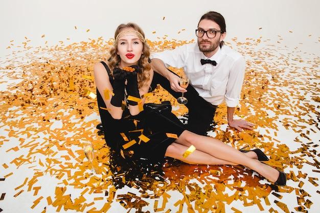 Giovane coppia elegante innamorata, seduta sul pavimento, lanciando coriandoli dorati