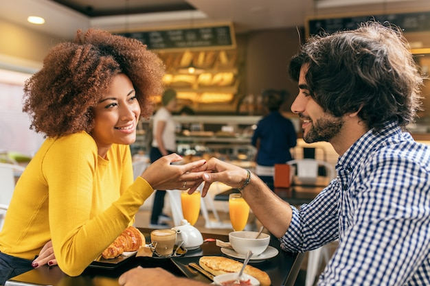 Giovane coppia facendo colazione al caffè, accarezzandosi la mano a vicenda, sono innamorati