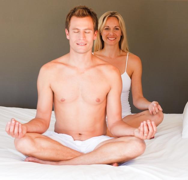 Giovane coppia facendo esercizi spirituali sul letto
