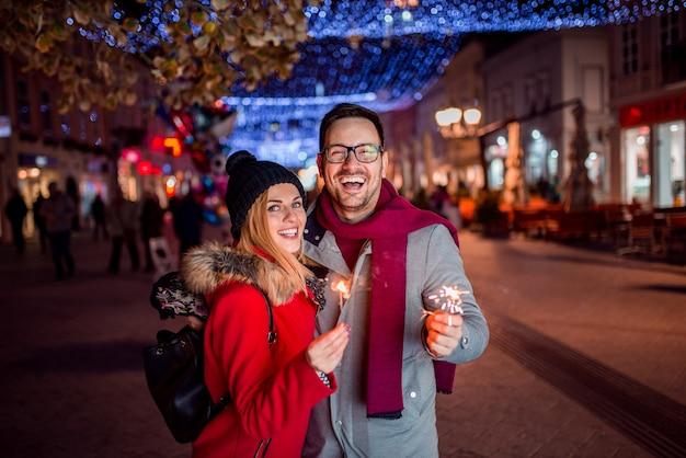 Giovane coppia godendo natale o capodanno vacanze all'aperto sulle strade della città.