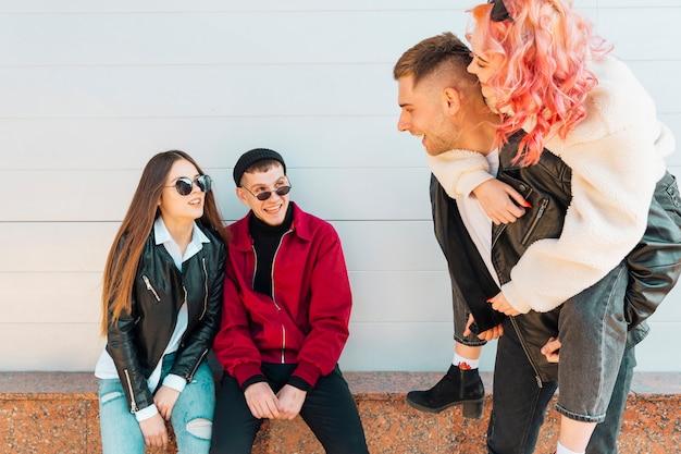 Giovane coppia guardando dare sulle spalle gli amici del giro