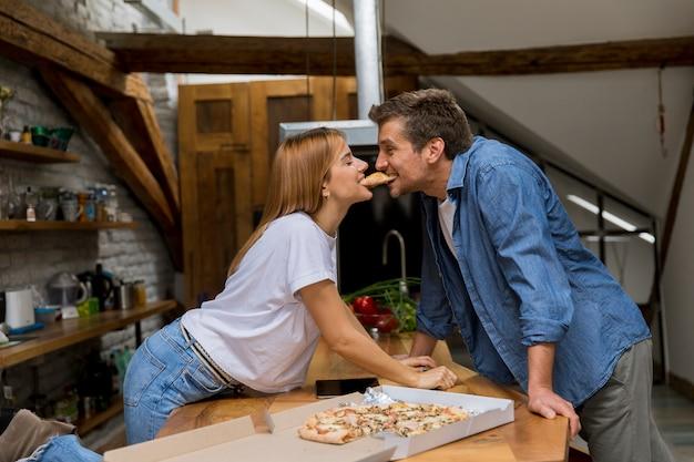 Giovane coppia in amore mangiando pizza in casa rustica