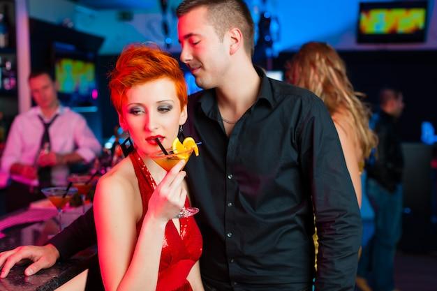 Giovane coppia in bar o club bevendo cocktail