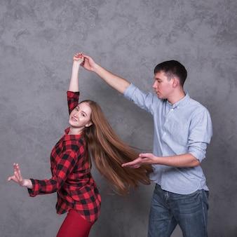 Giovane coppia in camicie danza