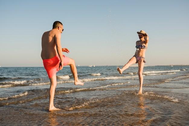 Giovane coppia in costume da bagno che spruzza l'acqua in spiaggia
