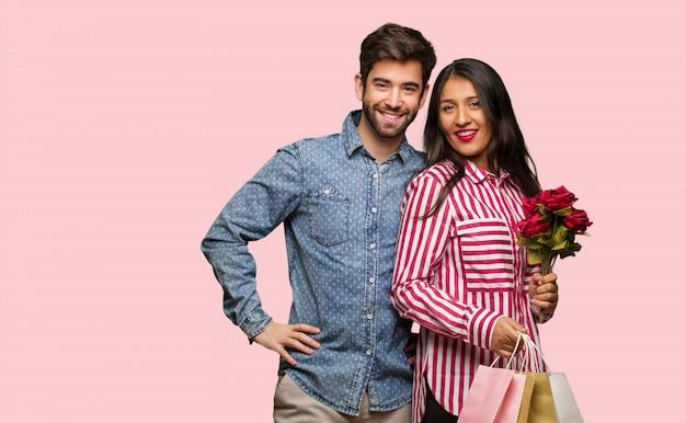 Giovane coppia in giorno di san valentino con le mani sui fianchi