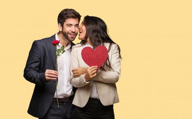 Giovane coppia in giorno di san valentino sussurrando sottotono gossip