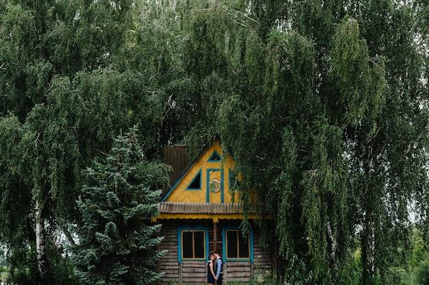 Giovane coppia in piedi, abbracciare e baciare vicino a una vecchia casa in legno