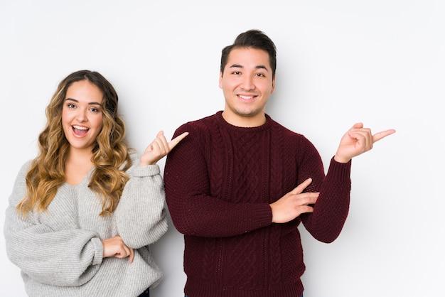 Giovane coppia in posa in un muro bianco sorridendo allegramente indicando con l'indice lontano.