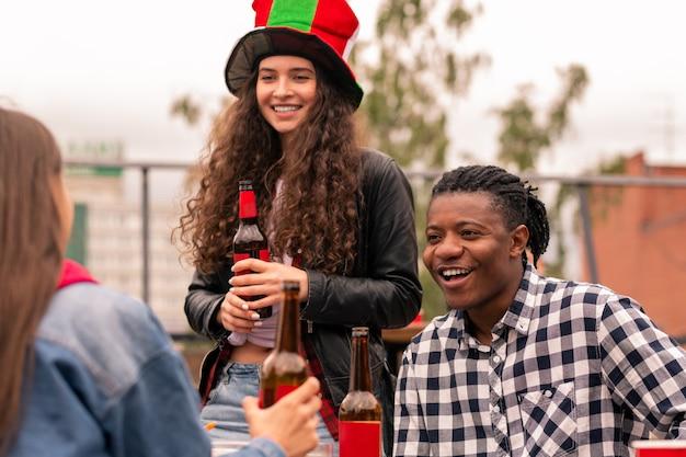 Giovane coppia interculturale di tifosi di calcio che bevono birra mentre chiacchierano con un amico dopo la trasmissione della partita