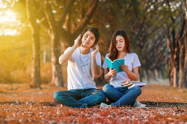 Giovane coppia leggendo un libro e ascoltare musica con cuffia nel parco