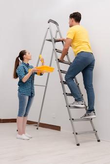 Giovane coppia pittura muro a casa