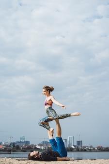Giovane coppia praticare yoga sullo sfondo della città