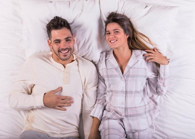 Giovane coppia ridendo nel letto