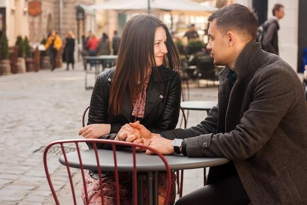 Giovane coppia seduta al caffè di strada