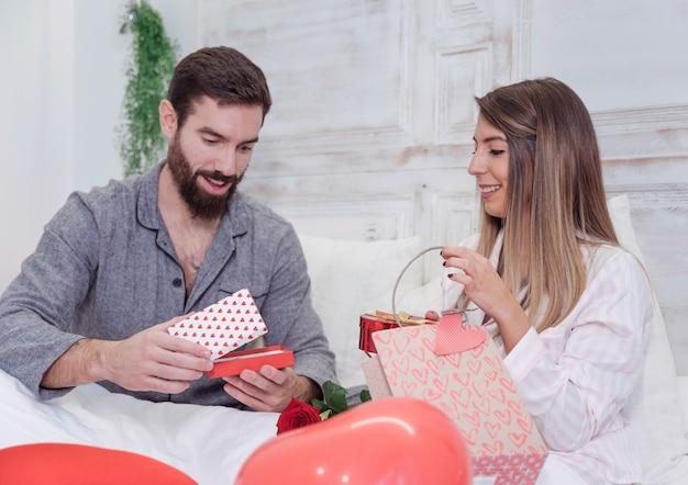 Giovane coppia seduta sul letto con regali