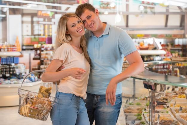 Giovane coppia shopping al supermercato - carrello di riempimento