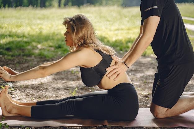 Giovane coppia sportiva facendo yoga fitness. persone in un parco estivo.