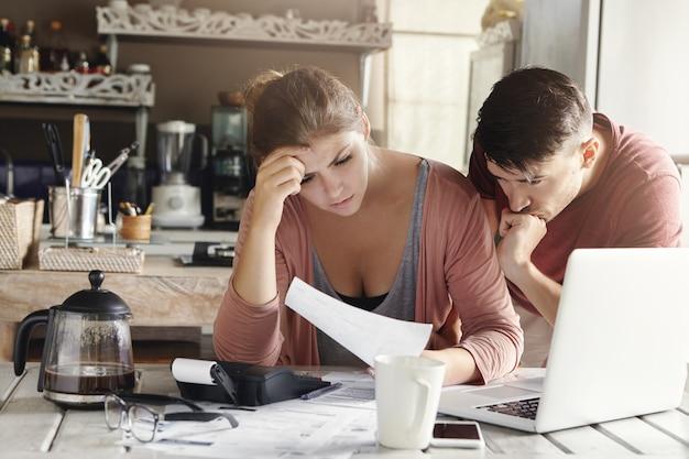 Giovane coppia sposata che affronta problema finanziario durante la crisi economica. donna frustrata e uomo infelice che studiano la bolletta in cucina, scioccati dall'importo da pagare per il gas e l'elettricità