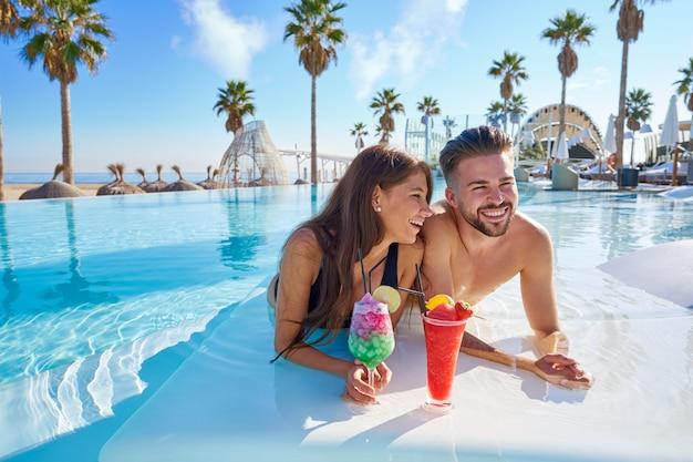 Giovane coppia sui cocktail piscina a sfioro