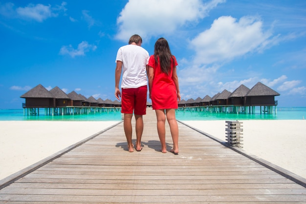 Giovane coppia sul molo spiaggia tropicale sull'isola perfetta