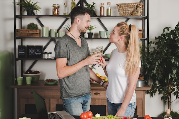 Giovane coppia tostatura flute di champagne in piedi in cucina
