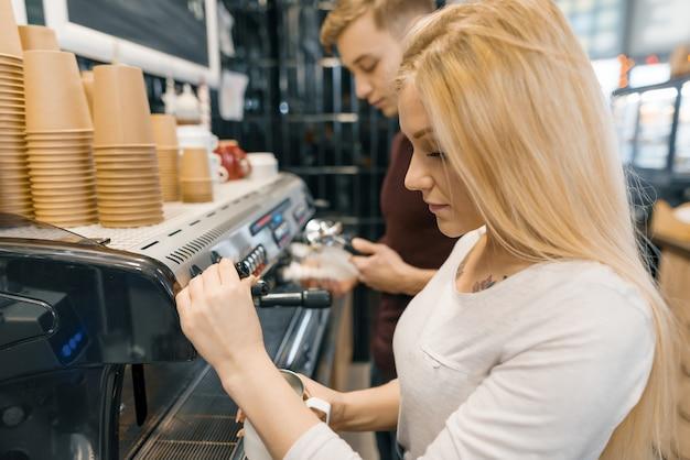 Giovane coppia uomo e donna proprietari piccola caffetteria, lavorando vicino a macchine da caffè.