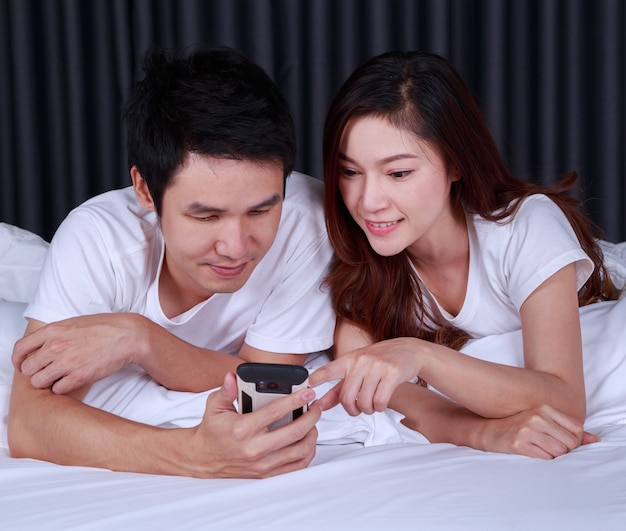 Giovane coppia utilizzando il telefono cellulare sul letto nella camera da letto