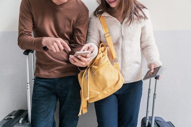 Giovane coppia viaggiatore con bagaglio e zaino utilizzando smartphone in aeroporto