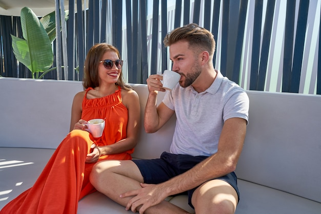Giovane copule che mangia caffè in lounge bar