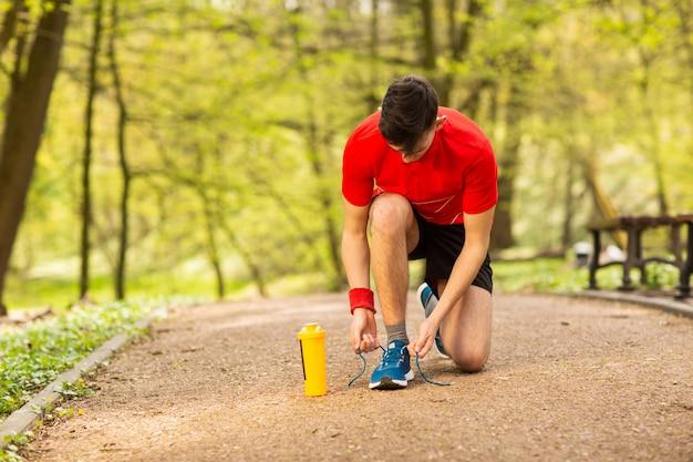 Giovane corridore bello che lega i laccetti sul parco della pista in primavera. vicino a lui c'è una termocoppia arancione