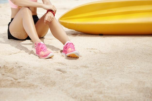 Giovane corridore femmina con bella pelle abbronzata in abiti sportivi e scarpe da ginnastica seduti sulla sabbia vicino alla barca gialla e rilassarsi dopo un intenso allenamento fisico all'aperto, prepararsi per la maratona