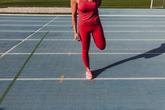 Giovane corridore irriconoscibile della donna di forma fisica che allunga le gambe sulla pista blu dello stadio al tramonto. sport e stile di vita sano concetto