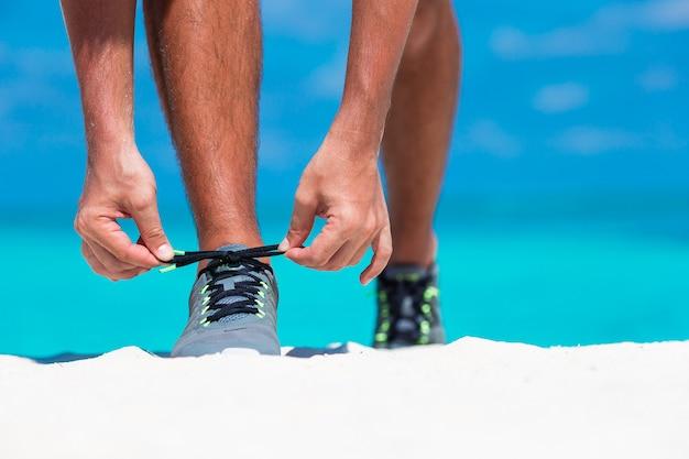 Giovane corridore maschio che si prepara per iniziare sulla spiaggia bianca