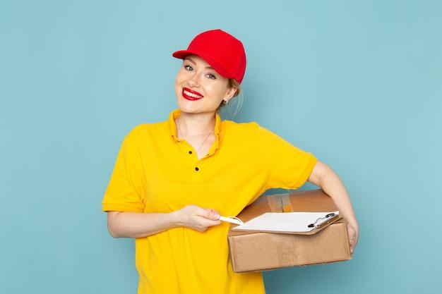 Giovane corriere femminile di vista frontale in camicia gialla e blocco note rosso del pacchetto della tenuta del mantello che sorride sul lavoro blu del pavimento