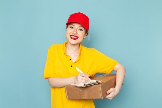 Giovane corriere femminile di vista frontale in camicia gialla e blocco note rosso del pacchetto della tenuta del mantello che sorride sul lavoro dello spazio blu