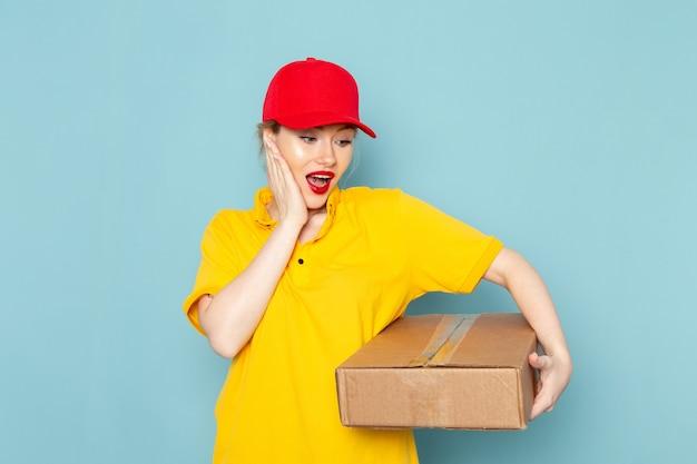 Giovane corriere femminile di vista frontale in camicia gialla e mantello rosso che sorride e che tiene pacchetto sullo spazio blu