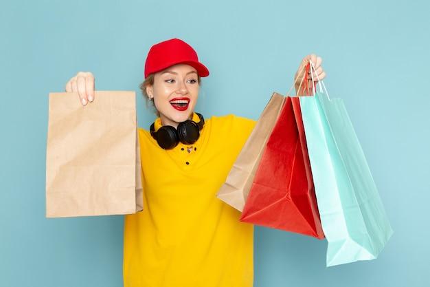 Giovane corriere femminile di vista frontale in camicia gialla e mantello rosso che tiene moltiplicare e pacchetti di acquisto sullo spazio blu