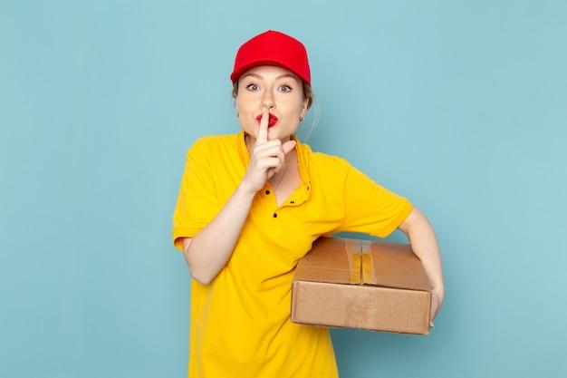 Giovane corriere femminile di vista frontale in camicia gialla e pacchetto rosso della tenuta del mantello sul lavoro di lavoro dello spazio blu