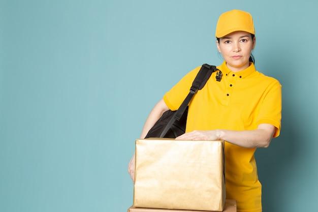 Giovane corriere femminile in t-shirt gialla tappo giallo tenendo la scatola sulla parete blu