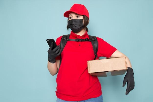 Giovane corriere in polo rosso berretto rosso maschera protettiva sterile nera zaino nero che tiene pacchetto usando il telefono sul blu