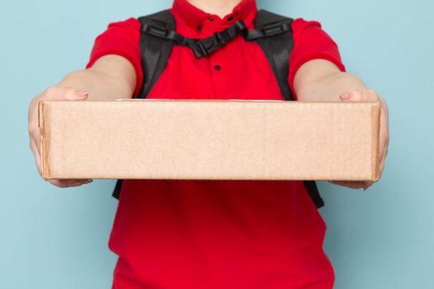 Giovane corriere in polo rosso berretto rosso zaino nero che tiene pacchetto su blu