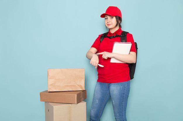 Giovane corriere in polo rosso berretto rosso zaino nero tenendo quaderno pacchetto su blu
