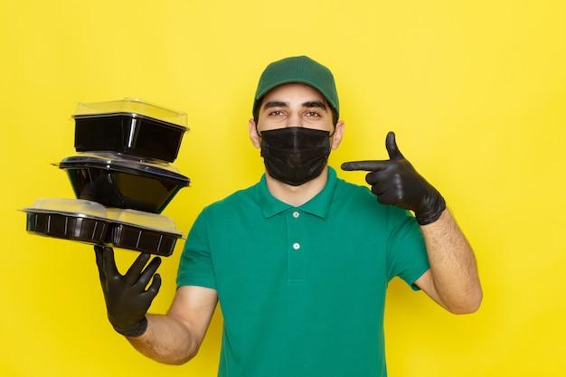 Giovane corriere maschio di vista frontale in cappuccio verde della camicia verde che tiene le ciotole dell'alimento nella maschera nera su giallo