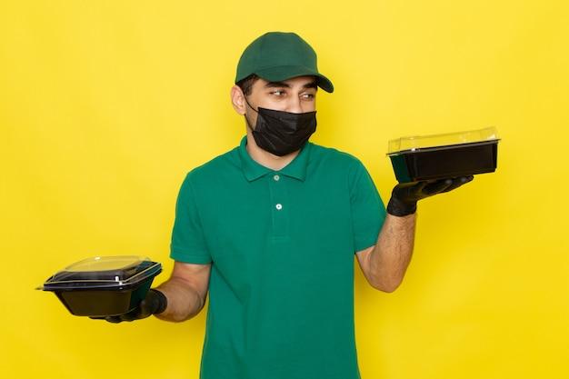 Giovane corriere maschio di vista frontale in cappuccio verde della camicia verde che tiene le ciotole dell'alimento nella maschera nera sul lavoro giallo