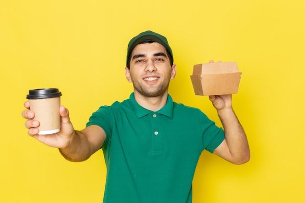 Giovane corriere maschio di vista frontale in pacchetto di consegna della tenuta del cappuccio verde della camicia verde e tazza di caffè che sorridono sul giallo