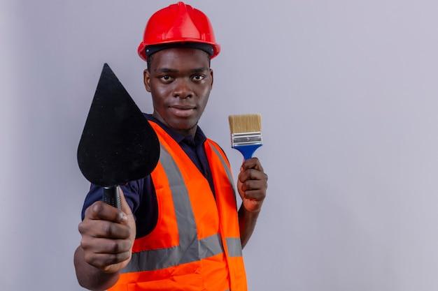Giovane costruttore afroamericano che indossa giubbotto di costruzione e casco di sicurezza che mostra spatola e tenendo il pennello guardando con un sorriso sicuro su bianco isolato