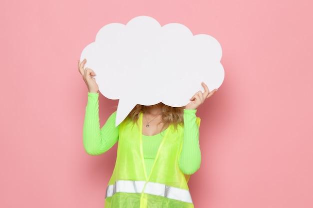 Giovane costruttore femminile di vista frontale nel casco giallo del vestito verde della costruzione che tiene il segno enorme bianco sul lavoro di costruzione di architettura di lavoro di spazio rosa