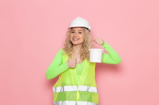 Giovane costruttore femminile di vista frontale nel casco verde del vestito della costruzione che tiene una vernice con il sorriso sui lavori di costruzione di architettura dello spazio rosa