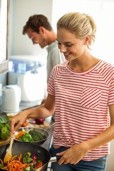 Giovane coupé felice che prepara alimento in cucina